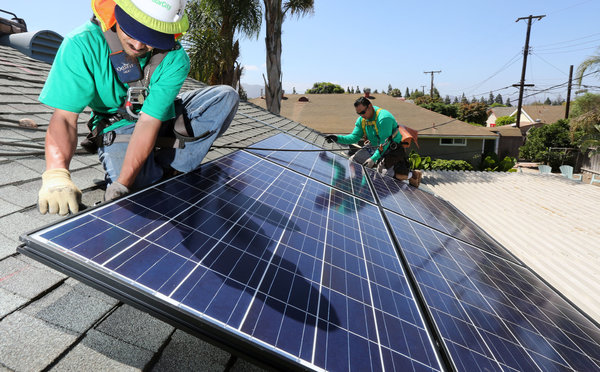 Workers for SolarCity installing solar panels (Image: JE Flores/NYTimes)