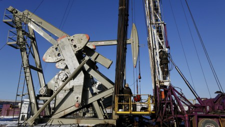A man climbs down an oil derrick on a rig of an oil drilling pump site in McKenzie County outside of Williston, North Dakota March 12, 2013 (Image: S. Stapleton/Reuters)