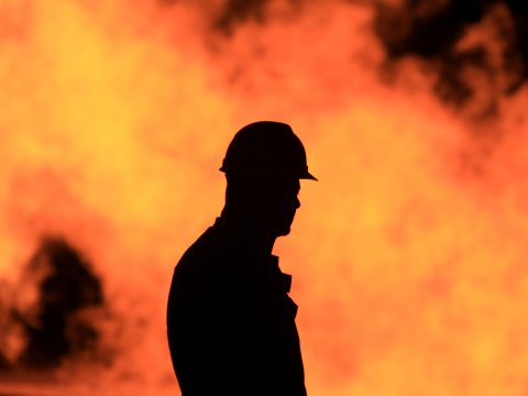 An unidentified oil worker walks in front of a natural gas flame burning off in the Persian Gulf desert oil field of Sakhir, Bahrain (Image: AP/H. Jamali)